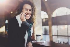 Jolie femme de sourire parlant avec des amis par son téléphone de cellules Bokeh et effet de fusées sur le fond brouillé Image stock