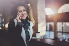 Jolie femme de sourire parlant avec des amis par son téléphone de cellules Bokeh et effet de fusées sur le fond brouillé Photographie stock libre de droits