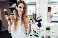 Jolie femme de sourire se tenant avec un grand choix de brosses de maquillage au studio de beauté photographie stock