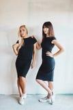Jolie femme deux dans une robe noire d'intérieur Photo stock
