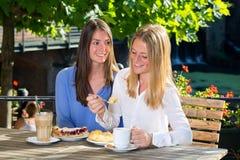 Jolie femme deux mangeant en café extérieur Photographie stock