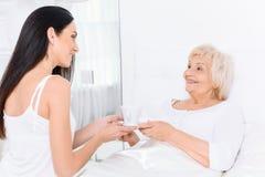 Jolie femme donnant dans sa tasse de grand-mère de thé Photographie stock libre de droits