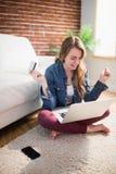 Jolie femme employant sa carte de crédit pour acheter en ligne Images stock