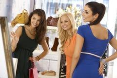 Jolie femme essayant sur la robe bleue au magasin de vêtements Photo stock