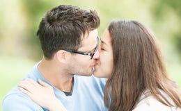 Jolie femme et homme en glaces embrassant en stationnement. Image libre de droits