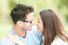 Jolie femme et homme en glaces embrassant en stationnement. Photos libres de droits