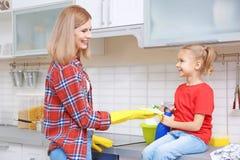 Jolie femme et sa fille lavant le fourneau électrique Photo libre de droits