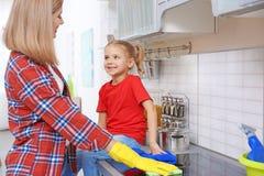 Jolie femme et sa fille lavant le fourneau électrique Image libre de droits
