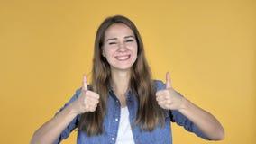 Jolie femme faisant des gestes des pouces d'isolement sur le fond jaune banque de vidéos