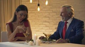 Jolie femme flirtant avec le millionnaire plus âgé pendant le dîner dans le restaurant banque de vidéos