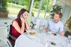 Jolie femme handicapée au téléphone avec le coleaguie au restaurant Images libres de droits