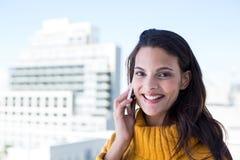 Jolie femme heureuse au téléphone image stock