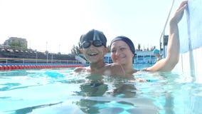 Jolie femme heureuse avec son fils dans la piscine banque de vidéos