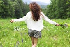Jolie femme heureuse de brune dans le domaine de camomille Photographie stock libre de droits