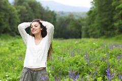 Jolie femme heureuse de brune dans le domaine de fleur Photographie stock libre de droits