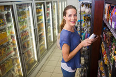 Jolie femme heureuse prenant un produit sur l'étagère Photographie stock libre de droits