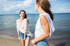 Jolie femme heureuse se tenant sur la plage riant à son ami Photo libre de droits