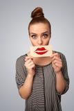 Jolie femme heureuse tenant la carte avec la marque de rouge à lèvres de baiser Photo stock
