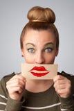 Jolie femme heureuse tenant la carte avec la marque de rouge à lèvres de baiser Image libre de droits