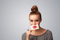Jolie femme heureuse tenant la carte avec la marque de rouge à lèvres de baiser Image stock