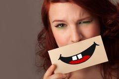 Jolie femme heureuse tenant la carte avec le smiley drôle Image stock