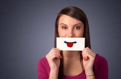 Jolie femme heureuse tenant la carte avec le smiley drôle images libres de droits