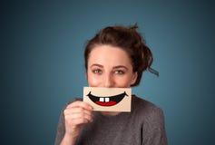 Jolie femme heureuse tenant la carte avec le smiley drôle photo stock