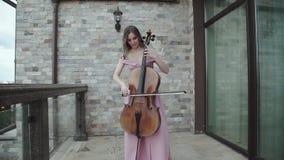 Jolie femme jouant avec enthousiasme sur le violoncelle sur le balcon banque de vidéos