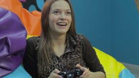 Jolie femme jouant le jeu vidéo, déchets de temps, habitude de jeu banque de vidéos