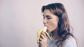 Jolie femme l'épluchage gris et en mangeant une banane banque de vidéos