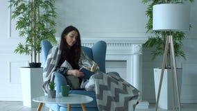 Jolie femme lisant un livre dans le fauteuil à la maison clips vidéos