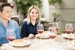 Jolie femme mangeant avec quelques amis Image stock