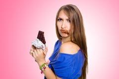 Jolie femme mangeant du chocolat avec deux mains, avec certains dans sa bouche Photos stock
