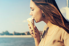 Jolie femme mangeant la crème glacée au-dessus du fond de l'eau d'océan de mer, Se photos libres de droits