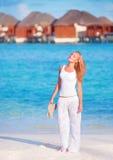 Jolie femme marchant le long de la plage Photographie stock libre de droits