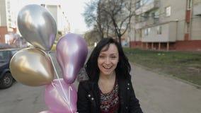 Jolie femme marchant le long de la rue tenant des ballons avec de l'hélium banque de vidéos