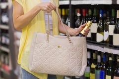 Jolie femme mettant une bouteille de champagne dans son sac Photo stock