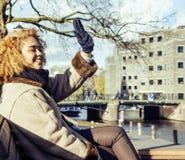 Jolie femme mignonne de mulâtre ondulant et souriant accueillant les amis, rues d'Amsterdam Photo libre de droits
