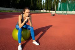 Jolie femme mince s'asseyant sur la boule convenable au stade L'espace vide photo libre de droits