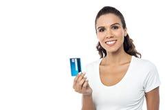 Jolie femme montrant la carte de crédit à l'appareil-photo Photo libre de droits