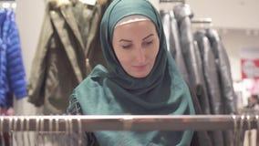 Jolie femme musulmane dans le hijab et avec un sac à dos sur des achats dans le magasin, fin  banque de vidéos