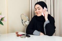 Jolie femme musulmane heureuse gaie reposant et à l'aide du téléphone portable mobile appelant pour l'ami causant pendant des vac image libre de droits