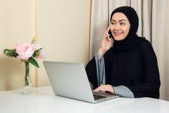 Jolie femme musulmane heureuse gaie reposant et à l'aide du téléphone portable mobile appelant pour l'ami causant pendant des vac photos libres de droits