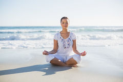 Jolie femme paisible en position de lotus sur la plage Images libres de droits