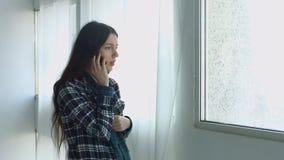 Jolie femme parlant au téléphone portable près de la fenêtre banque de vidéos