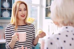 Jolie femme parlant avec sa mère tout en buvant du café Image stock