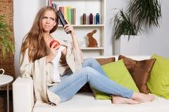Jolie femme pensant à regarder la TV Photographie stock libre de droits