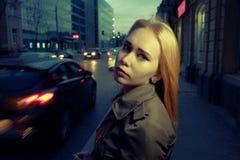 Jolie femme posant dans l'état d'esprit songeur dans la rue de nuit avec les voitures et les réverbères brouillés sur le fond, mo Photo libre de droits