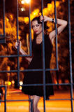Jolie femme posant dans la cage dehors la nuit Photographie stock libre de droits