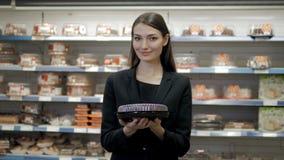 Jolie femme posant devant le contre- café et tarte de présentation au supermarché Photo libre de droits